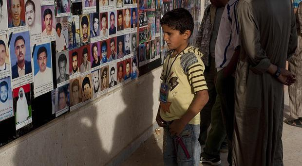 People look at portraits of people believed killed by Muammar Gaddafi's security forces, in Ajdabiya, Libya (AP)