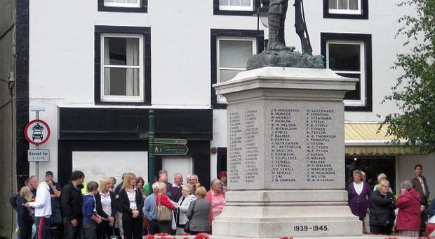A two-minute silence is held at Egremont War Memorial to mark the first anniversary of the shootings in which taxi driver Derrick Bird killed 12 people