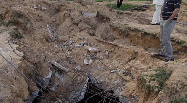 A Libyan official stands next to a crater left by a bunker bomb at Muammar Gaddafi's Bab al-Aziziya compound (AP)