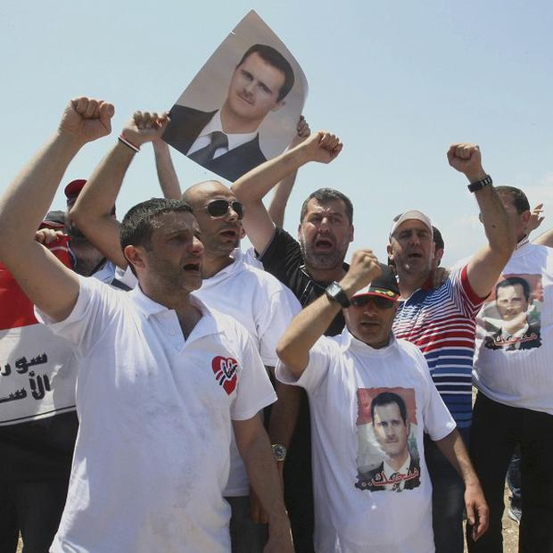 Supporters of Syrian President Bashar Assad demonstrate outside a hotel where the opponents of the Syrian regime gathered in Turkey (AP)