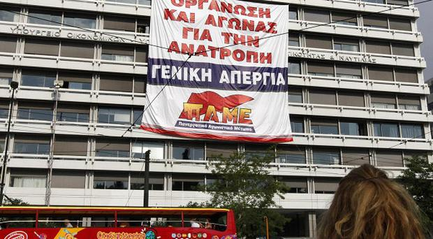 Protesters at Greece's finance ministry building display a giant banner calling for a general strike (AP)