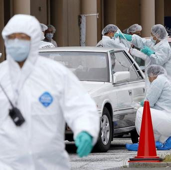 Cars are screened for leaked radiation from the tsunami-crippled Fukushima Dai-ichi nuclear plant in Fukushima prefecture, Japan (AP)