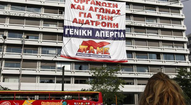 A giant banner calling for a general strike has been hung on the Greek Finance Ministry building in Athens (AP)
