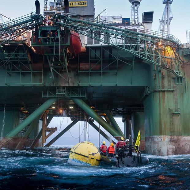 Greenpeace members have climbed a 53,000-ton oil rig in the Arctic waters off Greenland