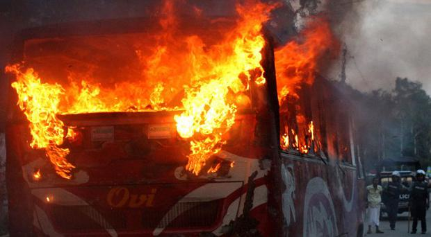 Flames rise from a bus set on fire by protesters in Dhaka, Bangladesh (AP)