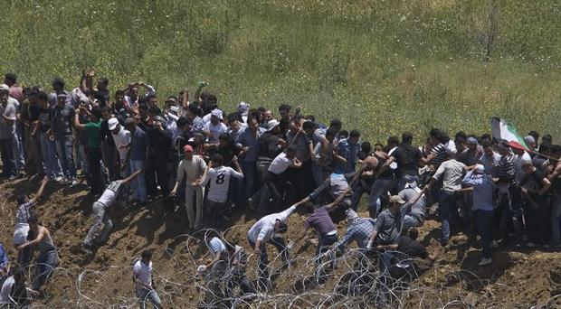 Pro Palestinian protesters try to break a fence along the border between Israel and Syria (AP)