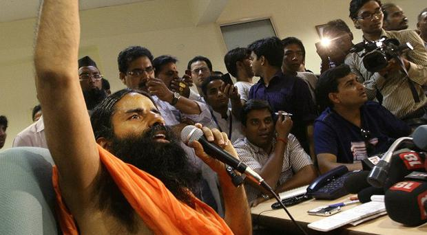 Indian yoga guru Baba Ramdev speaks to journalists as he continues his protest hunger strike at his ashram in Haridwar(AP)