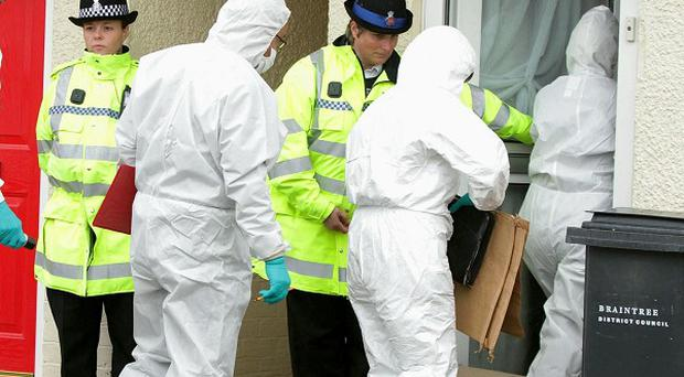 Police forensic officers enter a house in Braintree, Essex, after a woman and child were found dead