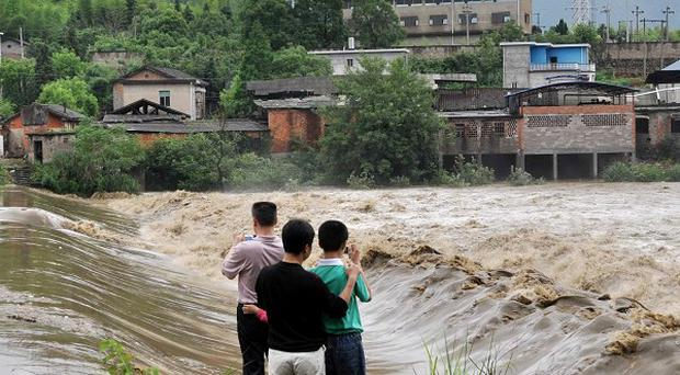 Rresidents examine flood waters in Dexing city, Jiangxi province, China