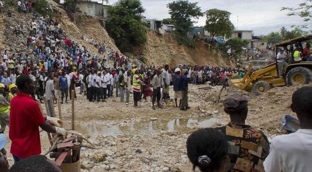 Residents watch rescue efforts after a deadly landslide was triggered by heavy rains in Port-au-Prince, Haiti (AP)
