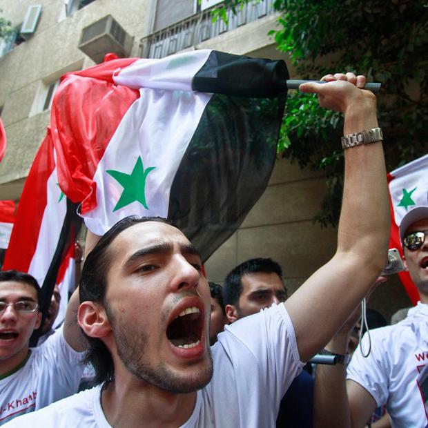 Syrian protesters shout slogans against President Bashar Assad in front of the Syrian embassy in Cairo(AP)