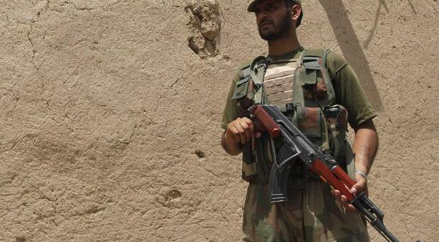 A Pakistan army soldier stands guard at the site of a blast in Matani, near Peshawar (AP)