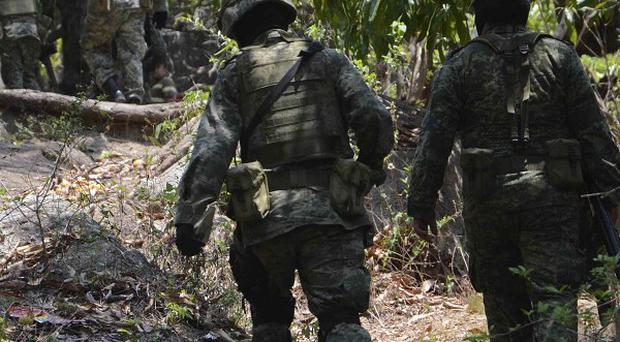 Mexican army soldiers walk up a hill after attending mass graves found in the Pacific resort city of Acapulco (AP)