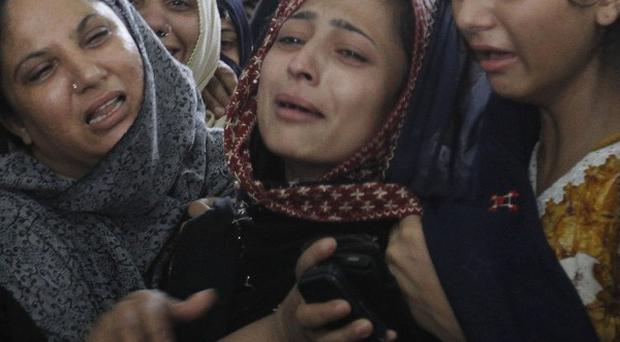 Family members mourn after an unarmed teenage boy was allegedly shot and died by the Pakistani miltary in Karachi (AP)