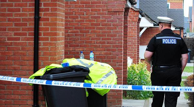 Police at a house in Stratford-upon-Avon where the bodies of a woman and five-year-old child were discovered