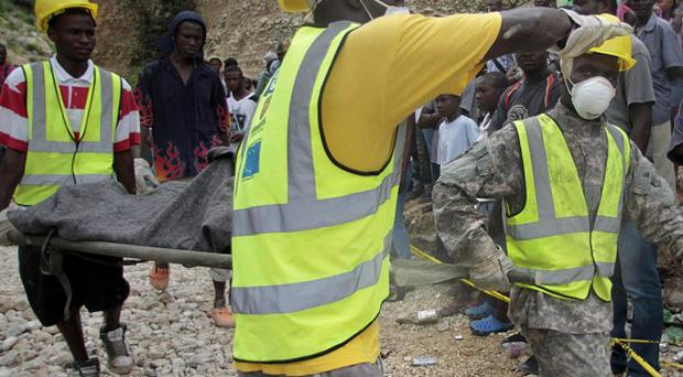 Rescue workers carry away the body of a person killed in a landslide after heavy rains in Port-au-Prince (AP)