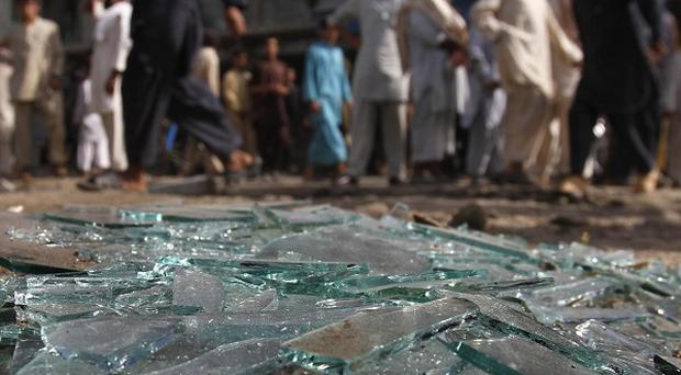 Afghans walk past the site of a bomb explosion in Laghman province east of Kabul, Afghanistan (AP)