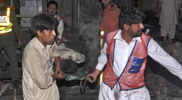 Pakistani rescue workers carry away a wounded man from the site of an explosion in Peshawar, Pakistan (AP)