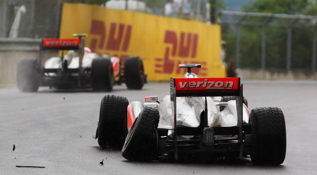 MONTREAL, CANADA - JUNE 12: Lewis Hamilton of Great Britain and McLaren suffers damage to his rear left wheel after driving too close to team mate Jenson Button of Great Britain and McLaren in the early stage of the Canadian Formula One Grand Prix at the Circuit Gilles Villeneuve on June 12, 2011 in Montreal, Canada. (Photo by Paul Gilham/Getty Images)