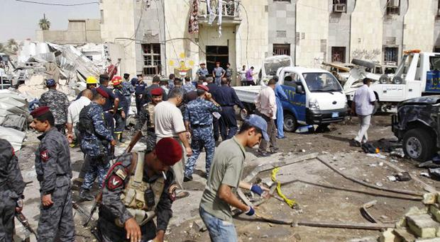 Security forces inspect the scene of a suicide car bomb attack in Basra (AP)