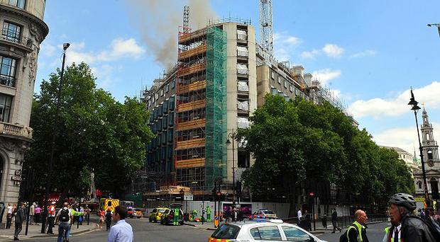 Smoke and flames rise from the roof of a building under construction on the Strand in London