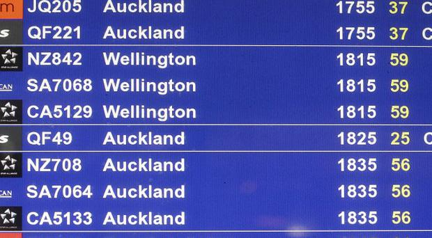 A departures board shows Qantas flights being cancelled at the international airport in Sydney (AP)