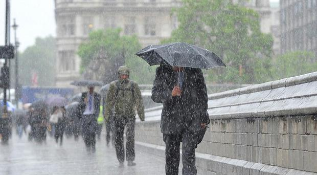 People struggle through the rain outside Parliament in London after a deluge abdruptly halted the spell of dry weather