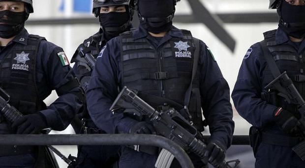 Federal police officers stand on guard during the presentation to the press of suspect 'El Wache', an alleged member of the Mexican Zetas drug cartel