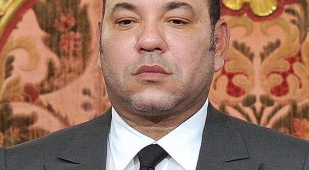 Morocco's King Mohammed VI listens to the national anthem after he delivered a speech to the nation on Friday
