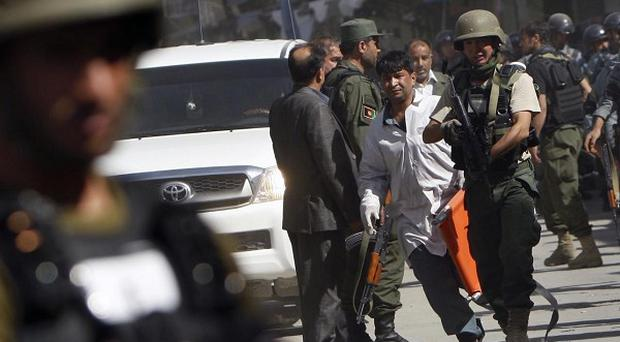 Afghan police officers secure an area close to a police station which came under attack in Kabul (AP)