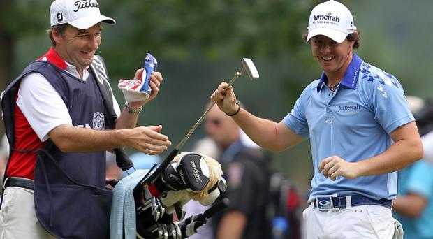 BETHESDA, MD - JUNE 19: Rory McIlroy of Northern Ireland takes his putter from his caddie J.P. Fitzgerald on the 13th hole during the final round of the 111th U.S. Open at Congressional Country Club on June 19, 2011 in Bethesda, Maryland. (Photo by Jamie Squire/Getty Images)
