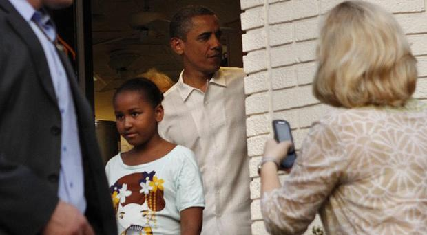 President Barack Obama and his daughter Sasha Obama exit the Thomas Sweet Ice Cream shop in the Georgetown neighborhood of Washington, on Father's Day, Sunday, June 19, 2011. (AP Photo/Jacquelyn Martin)