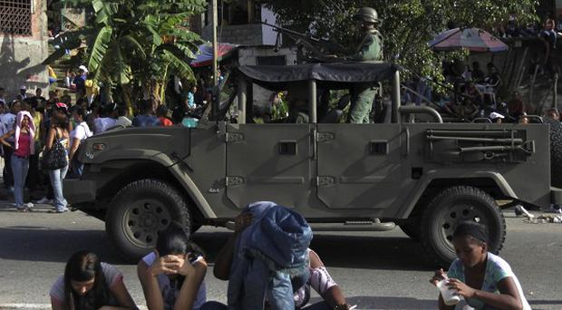 Soldiers in an patrol as relatives of inmates sit outside El Rodeo I prison in Guatire, Venezuela