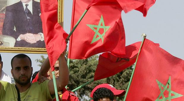 Pro-government demonstrators hold a poster of Morocco's king as they celebrate constitutional reforms recently unveiled by the king