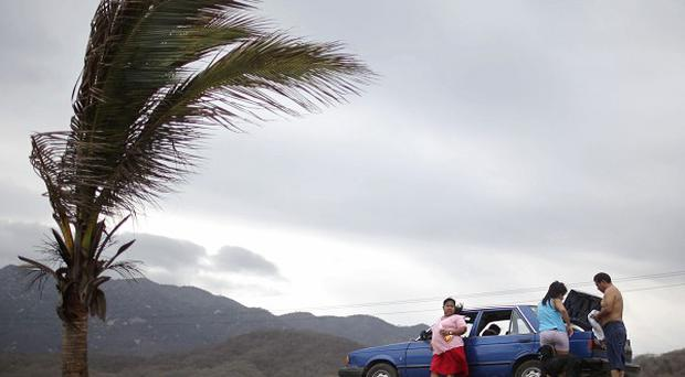 Tourists leave Miramar beach in Manzanillo, Mexico, ahead of the storm's arrival (AP)