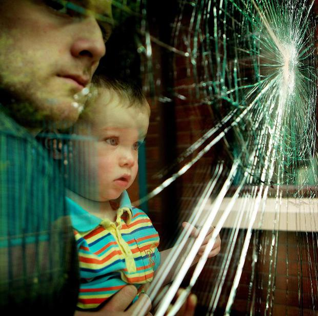 Martin Ferguson and his godson Jude Millen look out from the shattered window after a night of rioting (PA)