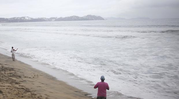Men fish along the Playa de Oro shore in the Pacific resort city of Manzanillo, Mexico (AP)