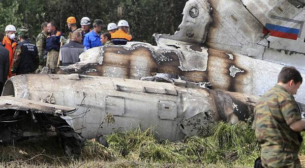 Forensic experts examine the plane wreckage (AP)