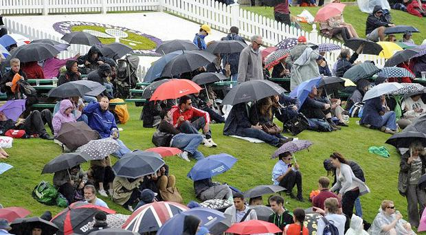 Spectators use umbrellas on Murray Mount as the rain starts to fall