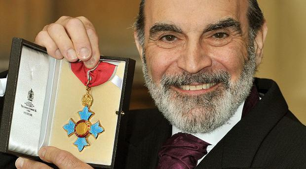 David Suchet proudly holds his CBE after a Buckingham Palace ceremony