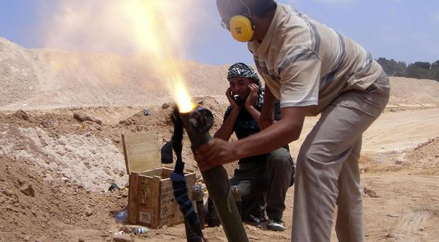 Rebel fighters fire their mortars towards pro-Gaddafi forces on the front line at Misrata, Libya (AP)