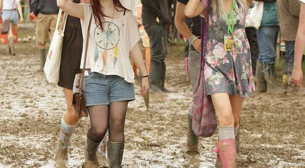 Glastonbury began with a squelch as the first arrivals at Britain's biggest music festival were forced to contend with a giant mudbath