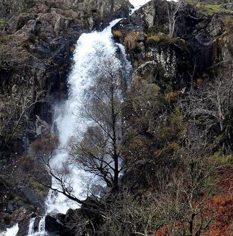 A woman has been badly injured falling about 60 feet down a cliff