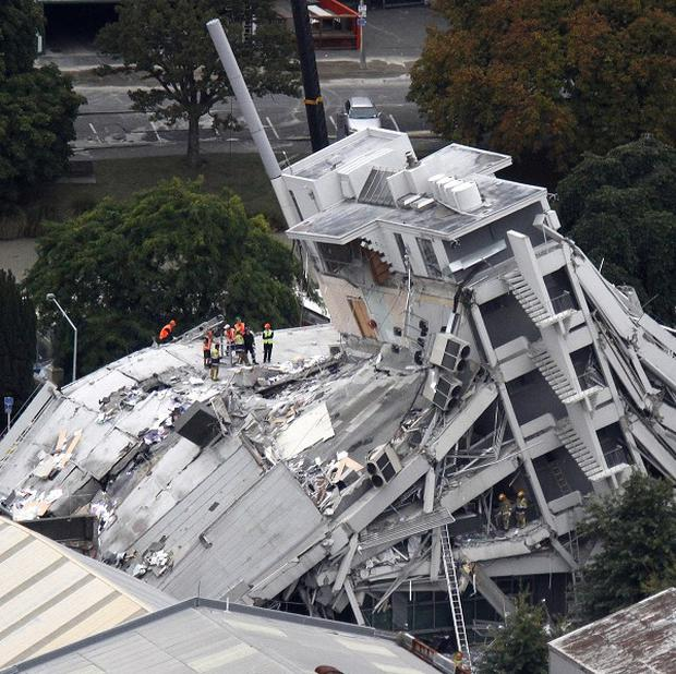 Rescue workers climb on to the collapsed Pyne Gould Guinness Building in central Christchurch after February's quake (AP)