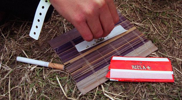 File photo dated 25/06/2000 of a reveller rolling a joint at the Glastonbury Music Festival in Pilton, Somerset