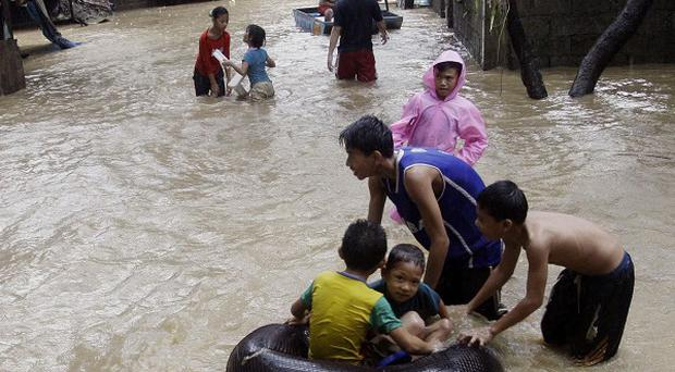 Children enjoy the knee-deep water on a submerged street in suburban San Mateo east of Manila in the Philippines (AP)