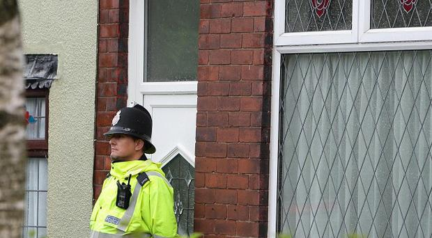 Police at the scene where a suspected burglar was stabbed to death while trying to break into a house