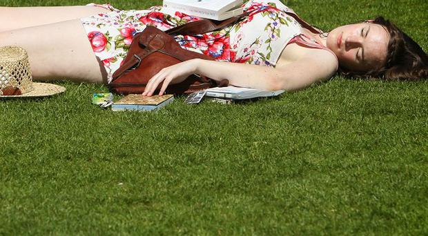 A woman relaxes in the sun as people enjoy the hot weather on the South Bank in central London