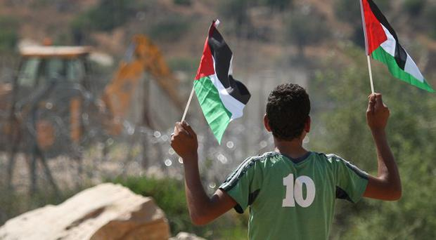A Palestinian boy holds Palestinian flags as an Israeli tractor removes parts of a section of Israel's separation barrier near Bilin (AP)