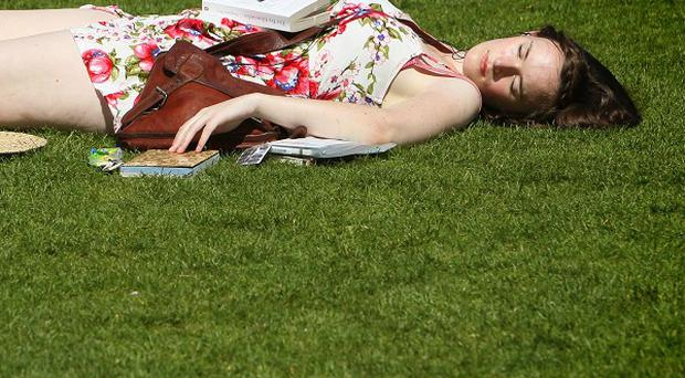 A woman relaxes in the sun on the South Bank in central London
